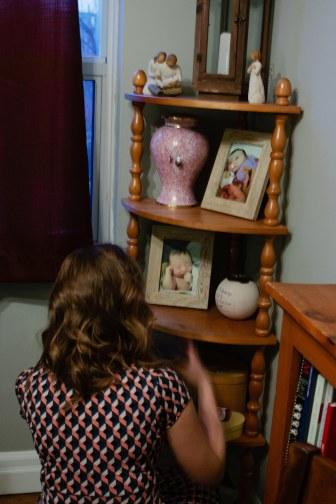 Vanessa crouches to retrieve memorabilia of her daughter, Leah.